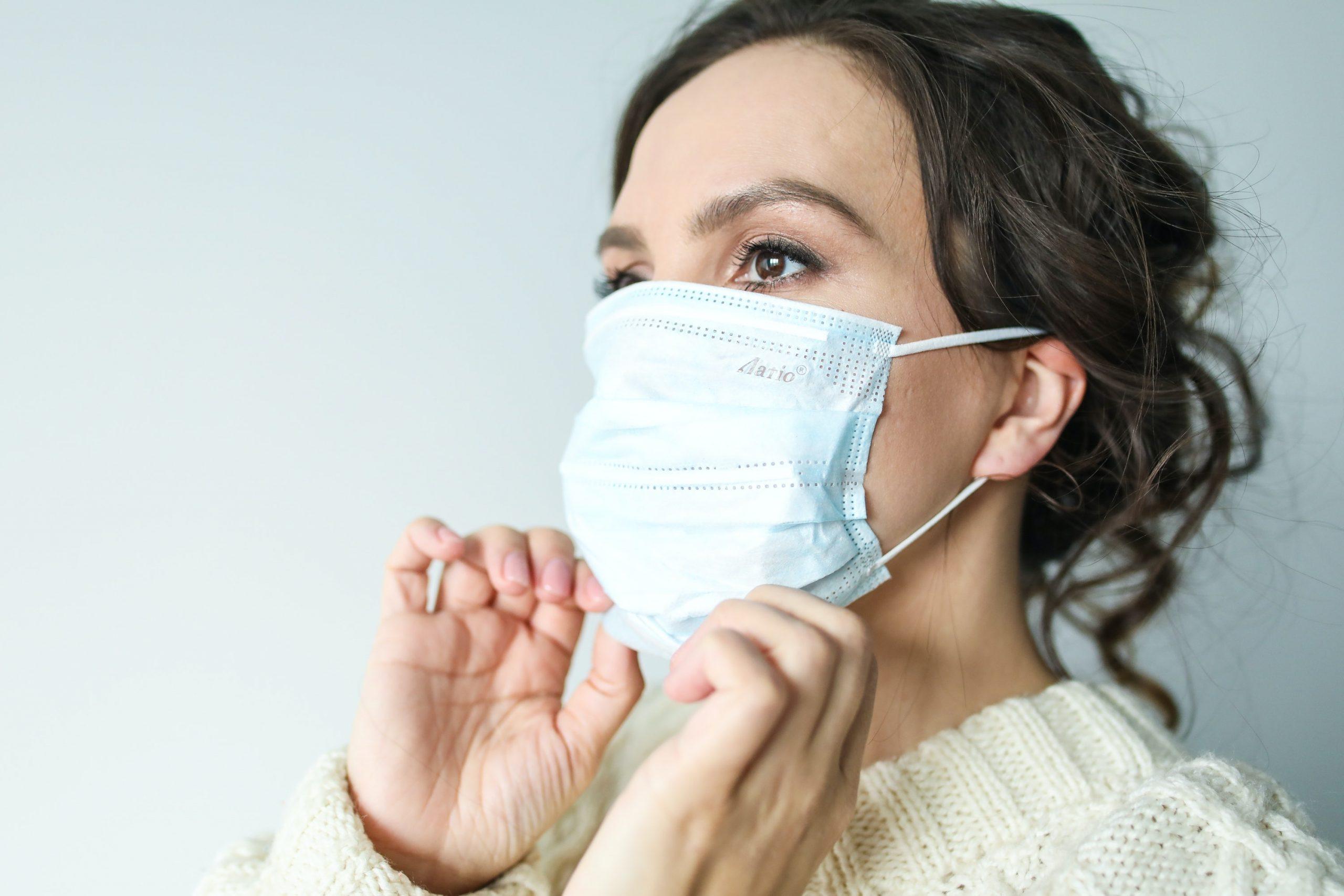 Woman adjusts mask.